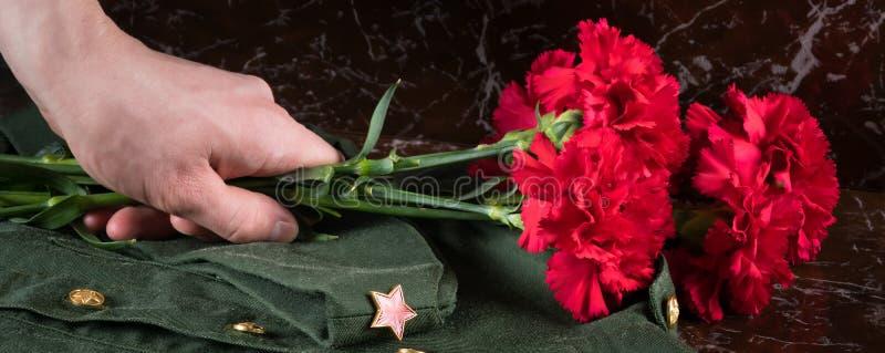 A mão põe flores vermelhas sobre um uniforme militar, close-up fotos de stock