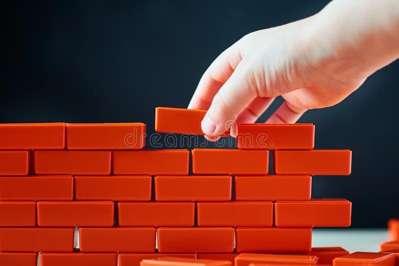 A mão põe o último tijolo sobre uma parede Conceito da construção e da construção fotos de stock royalty free