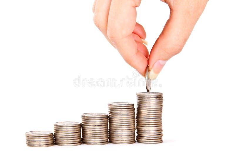 A mão põr a moeda à escadaria do dinheiro foto de stock