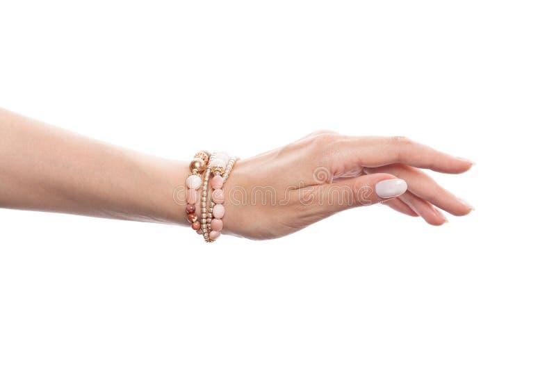 Mão perfeita da mulher que veste o bracelete dourado com opalas, as pérolas cor-de-rosa e os grânulos do ouro isolados no fundo b fotos de stock royalty free