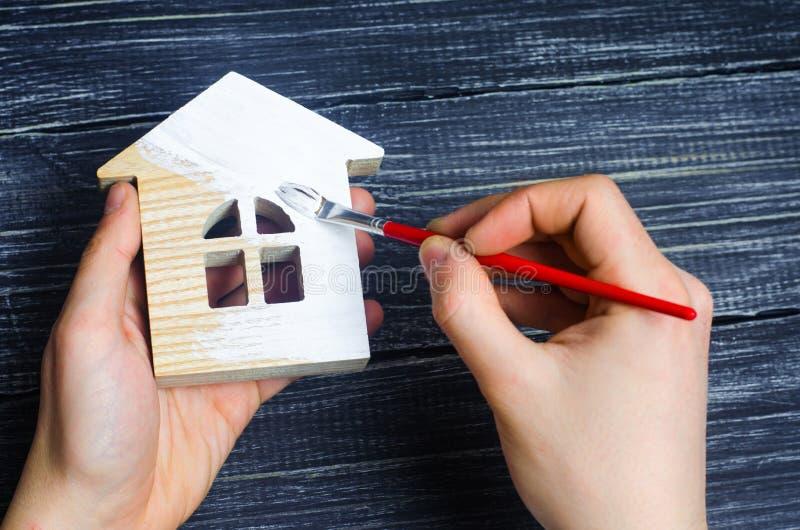 A mão pinta uma casa Conceito do reparo, passatempo, trabalho reparo fotografia de stock royalty free