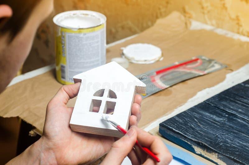 A mão pinta uma casa Conceito do reparo, passatempo, trabalho reparo foto de stock royalty free