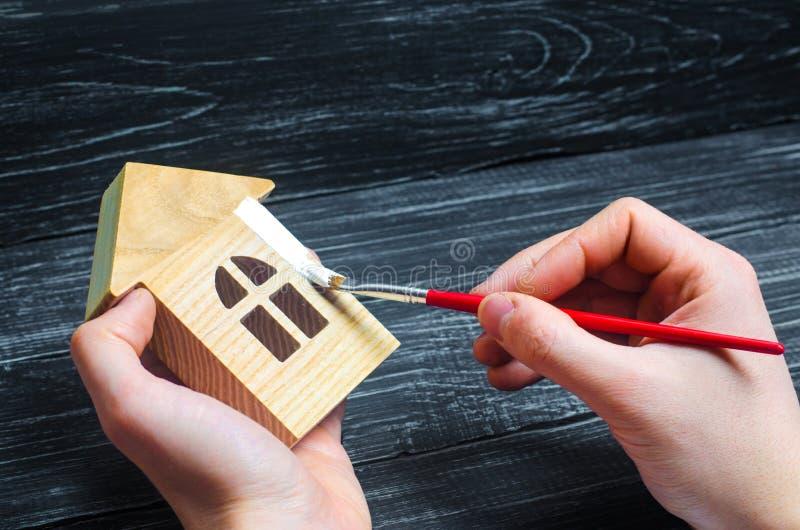 A mão pinta uma casa Conceito do reparo, passatempo, trabalho reparo fotografia de stock
