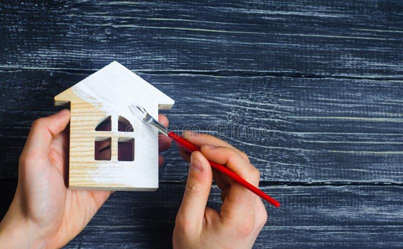 A mão pinta uma casa Conceito do reparo, passatempo, trabalho Repare e foto de stock