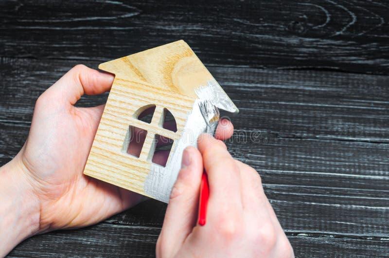 A mão pinta uma casa Conceito do reparo, passatempo, trabalho Repare e fotos de stock royalty free