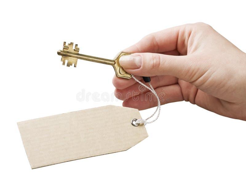 A mão prende uma chave com uma etiqueta fotografia de stock