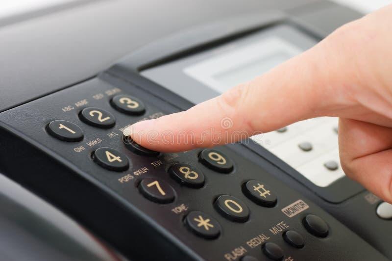 A mão pressiona a tecla do fax fotos de stock
