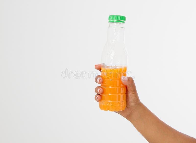 Mão preta que mantém uma garrafa do suco isolada em um fundo branco Front View Zombaria acima Copie o espaço molde blank imagem de stock royalty free