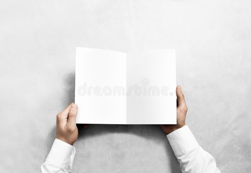 Mão que abre o modelo branco vazio da brochura do folheto foto de stock royalty free