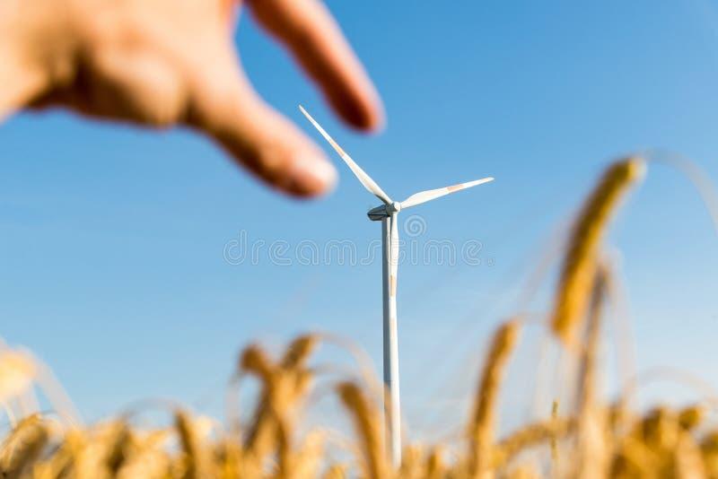 Mão que agarra a lâmina de uma turbina eólica imagem de stock