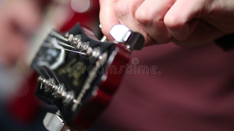 Mão que ajusta a guitarra elétrica do headstock filme