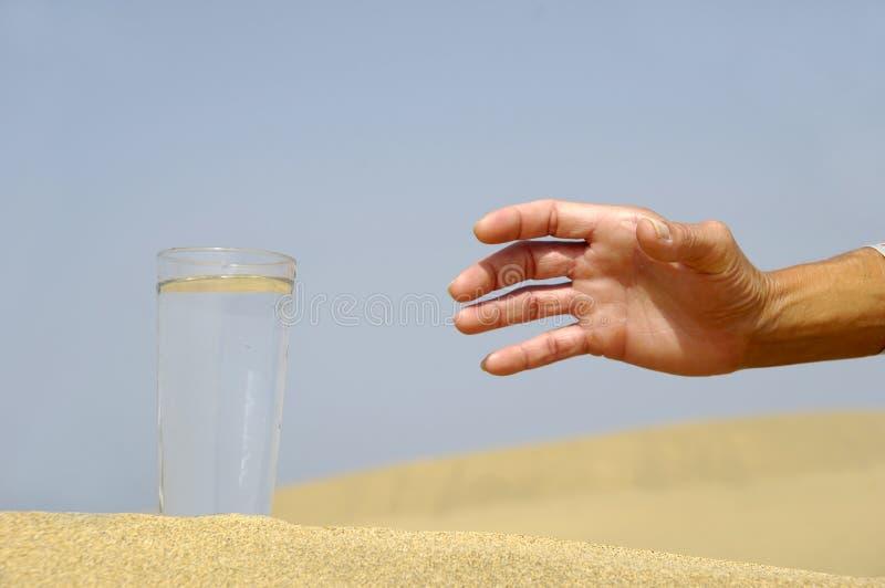 Mão que alcanga para a água. imagem de stock