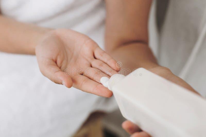 Mão que aplica o creme hidratando Jovem mulher na garrafa branca da terra arrendada de toalha com loção ou no creme no banheiro C imagem de stock