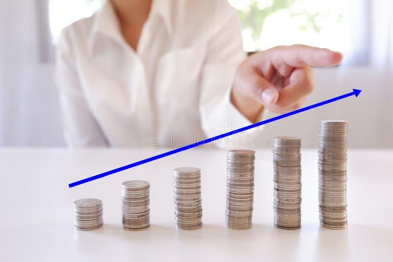 Mão que aponta a pilha crescente do dinheiro de aumento das moedas foto de stock