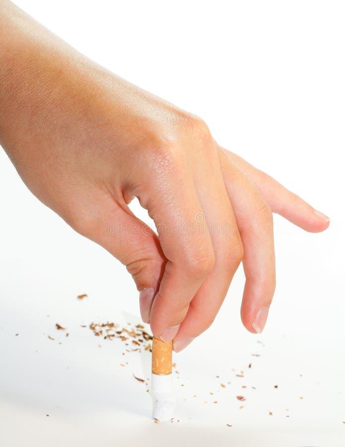 Mão que arranca para fora um cigarro fotografia de stock