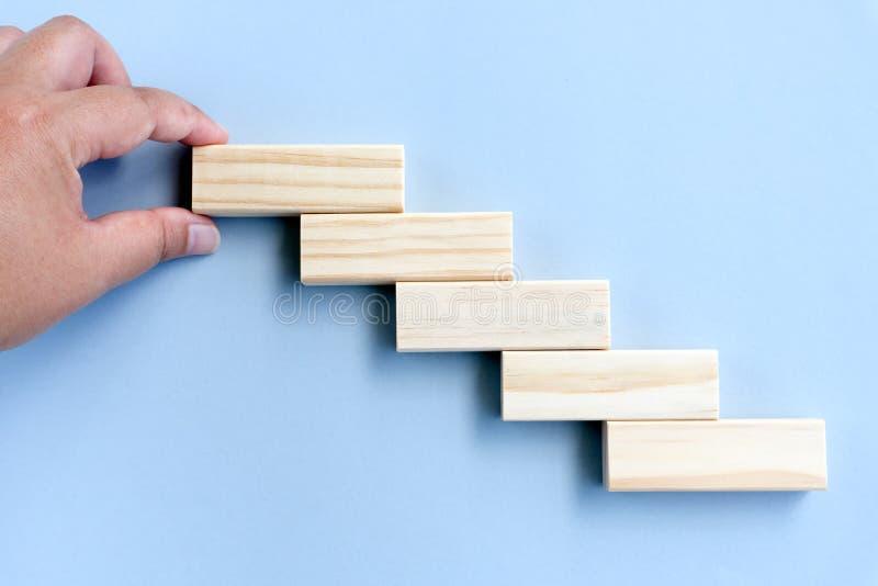 Mão que arranja o bloco de madeira que empilha como a escada da etapa imagens de stock