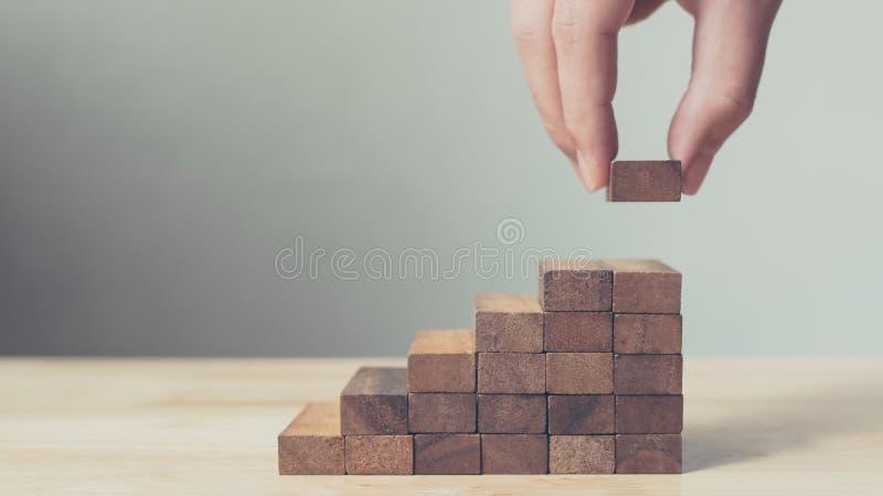 Mão que arranja o bloco de madeira que empilha como a escada da etapa Carreira da escada imagem de stock royalty free