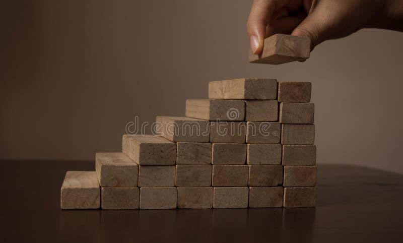 Mão que arranja o bloco de madeira que empilha como a escada da etapa na tabela de madeira imagens de stock royalty free