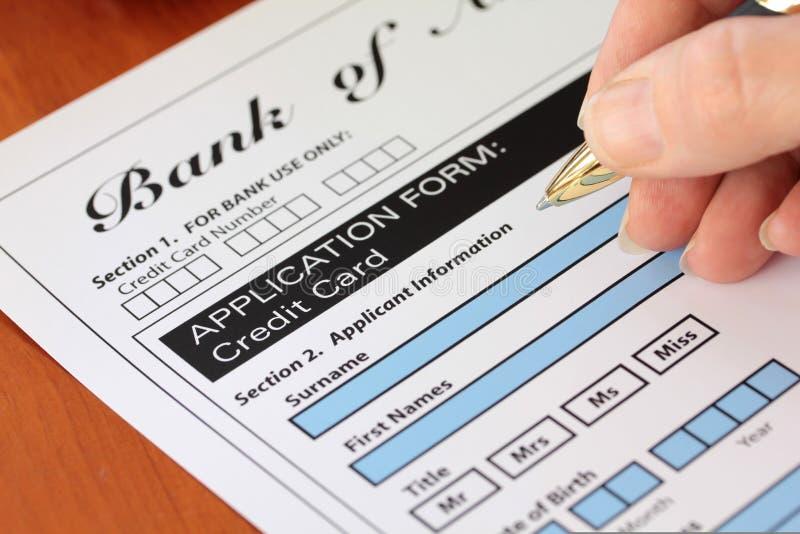 Mão que assina uma aplicação fictícia do cartão de crédito fotografia de stock