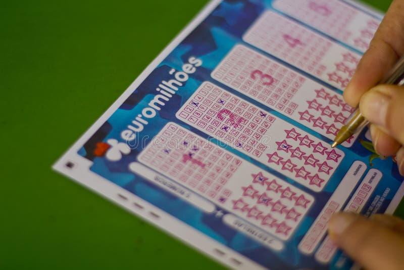 Mão que completa um bilhete de loteria Euromillions fotografia de stock royalty free