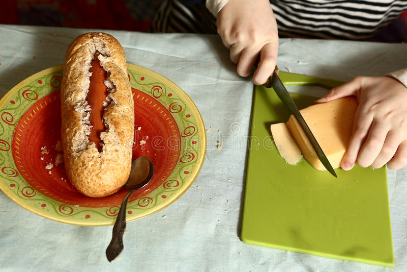 Mão que cozinha o cachorro quente com queijo do baguette da salsicha fotografia de stock royalty free