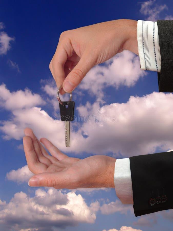 A mão que dá a chave da casa fotos de stock royalty free