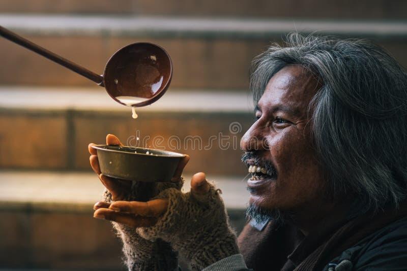 A mão que dá o alimento para fazer o homem com fome desabrigado tem a cara feliz com sorriso foto de stock