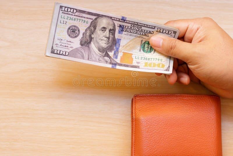 Mão que dá o dinheiro com a carteira na tabela de madeira imagens de stock