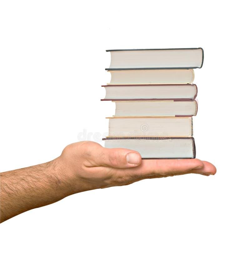 Mão que dá a pilha do livro imagem de stock
