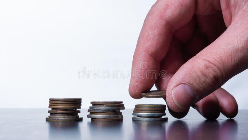 Mão que empilha moedas pequenas em uma tabela fotografia de stock