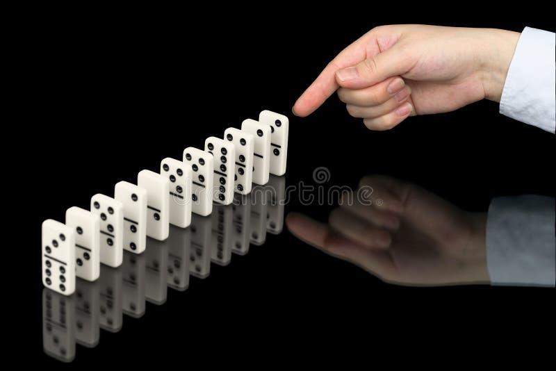 Mão que empurra contadores dos dominós no preto fotos de stock