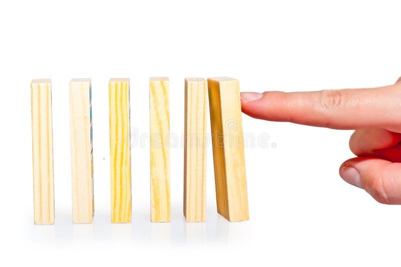 Mão que empurra a fileira dos dominós alinhados imagem de stock