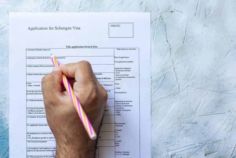 Mão que enche o formulário de candidatura do visto de Schengen fotografia de stock royalty free