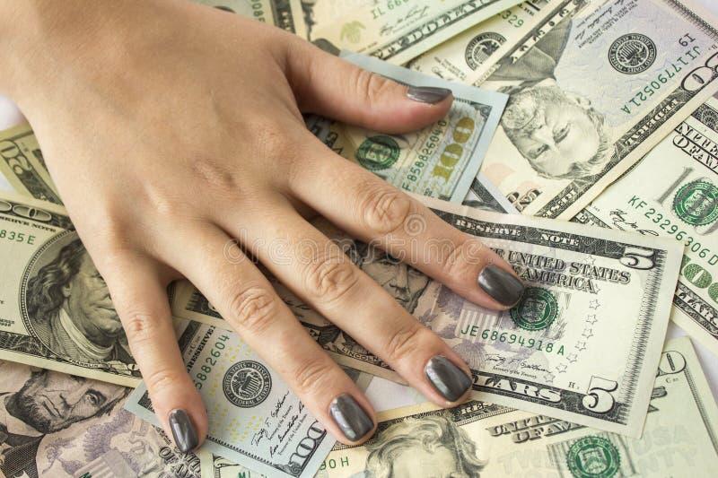 Mão que encontra-se em notas de dólar Fundo do dinheiro fotos de stock