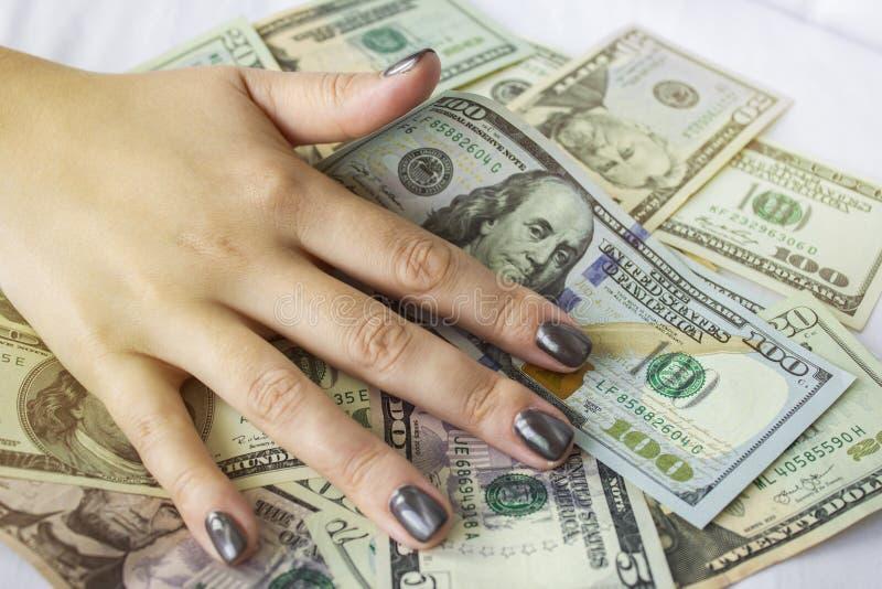 Mão que encontra-se em notas de dólar Fundo do dinheiro imagem de stock royalty free