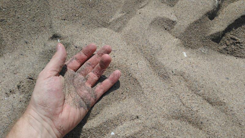 Mão que encontra-se no dia ensolarado da areia imagem de stock