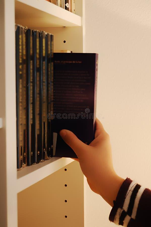 Mão que escolhe um livro de uma prateleira fotografia de stock royalty free