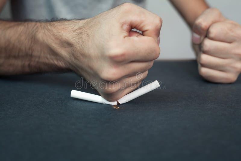 Mão que esmaga o cigarro imagem de stock