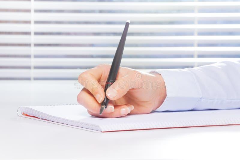 Mão que faz anotações no caderno do anel-limite fotos de stock royalty free