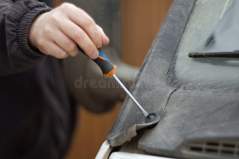 Mão que fixa uma capota do carro fotos de stock royalty free