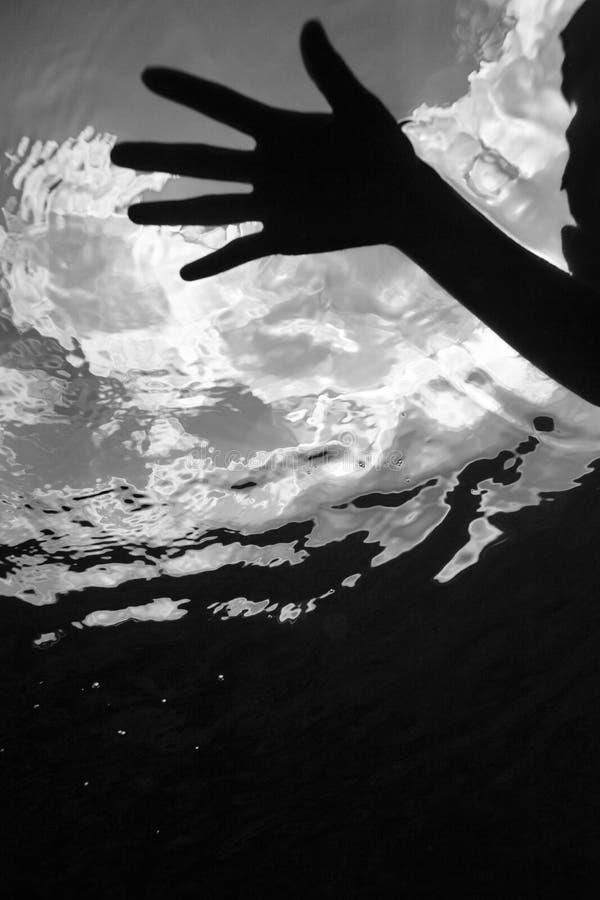 Mão que flutua debaixo d'água. imagem de stock
