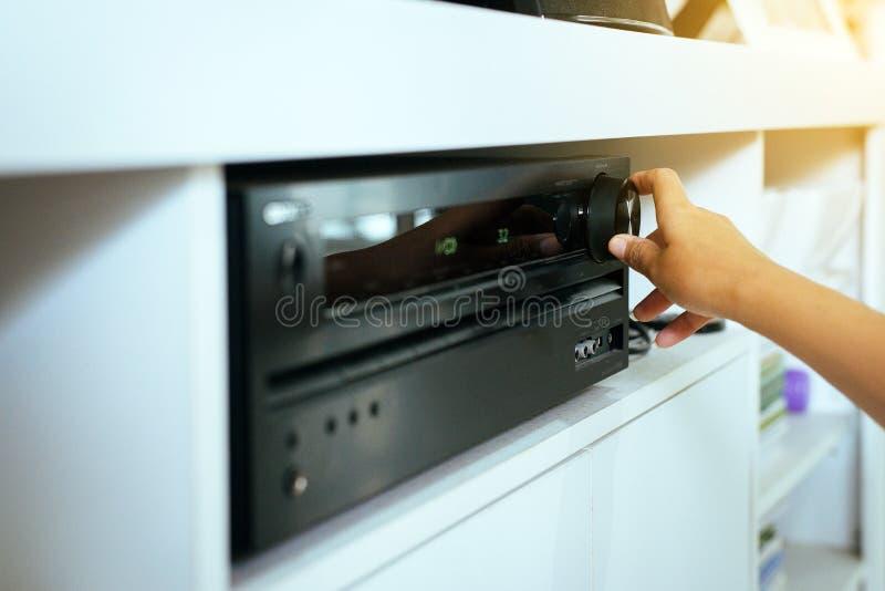 Mão que gira sobre o amplificador do cinema em casa imagem de stock