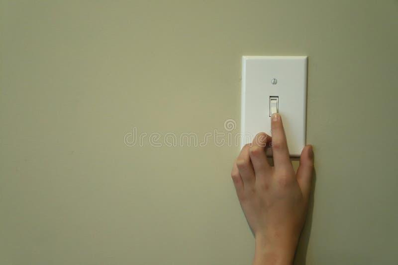 Mão que gira sobre o interruptor da luz fotografia de stock royalty free