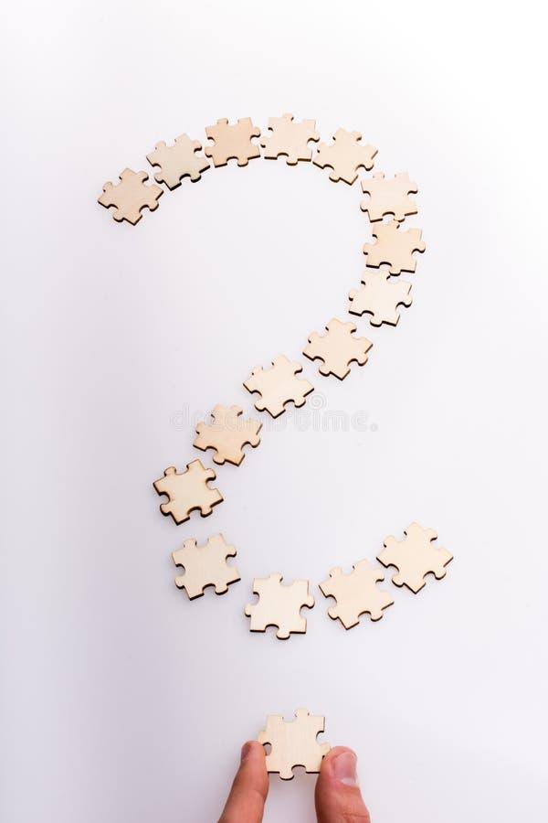 Mão que guarda a última parte de ponto de interrogação Ponto de interrogação feito das partes do enigma no fundo branco imagem de stock royalty free