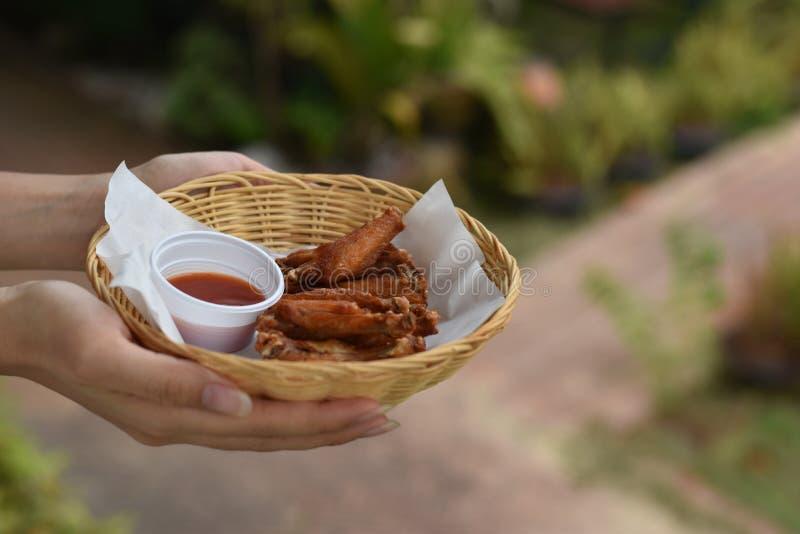 Mão que guarda as asas de frango frito com mergulhos em uma cesta fotos de stock royalty free
