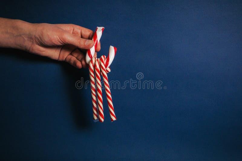 Mão que guarda bastões de doces no fundo azul imagem de stock