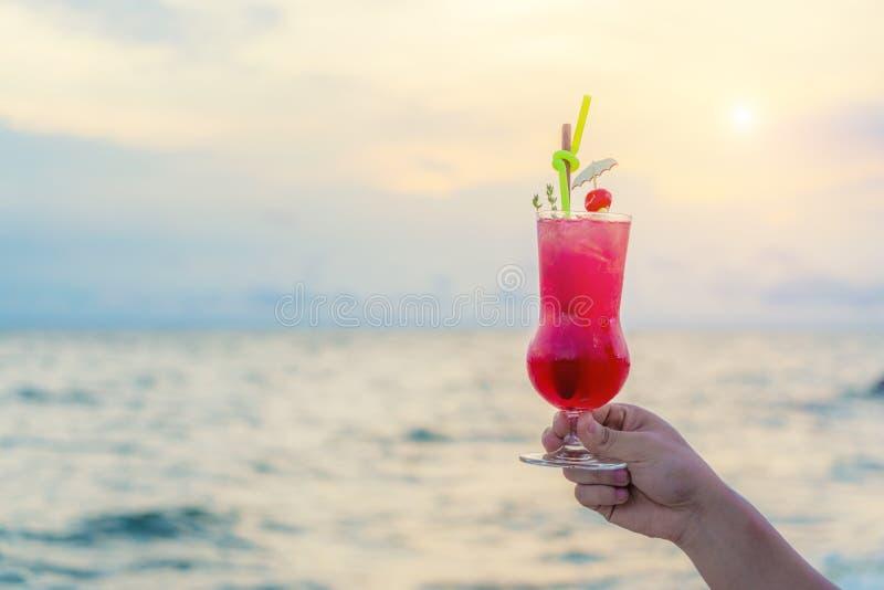 Mão que guarda a bebida vermelha do cocktail no fundo crepuscular do mar & do céu Conceito do verão, das férias, do curso e do fe imagem de stock royalty free