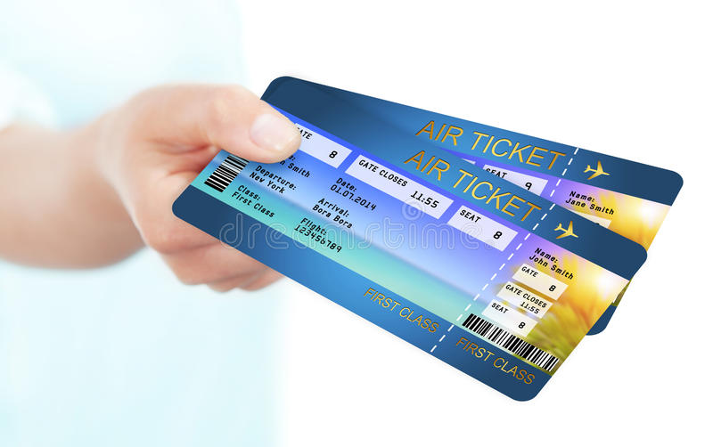 Mão que guarda bilhetes da passagem de embarque da linha aérea do feriado foto de stock royalty free