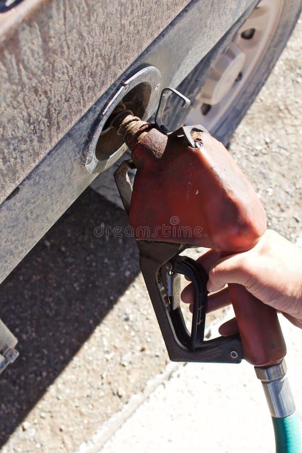 Mão que guarda a bomba de combustível diesel foto de stock