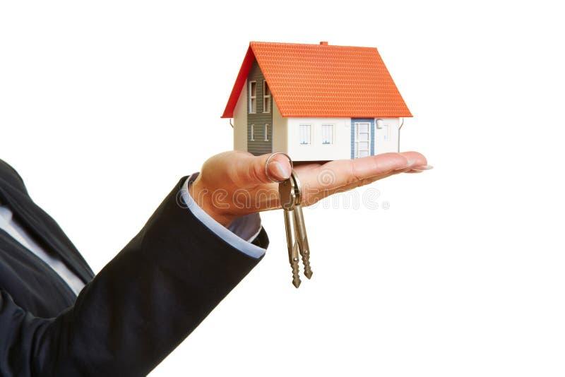 Mão que guarda a casa e as chaves fotografia de stock